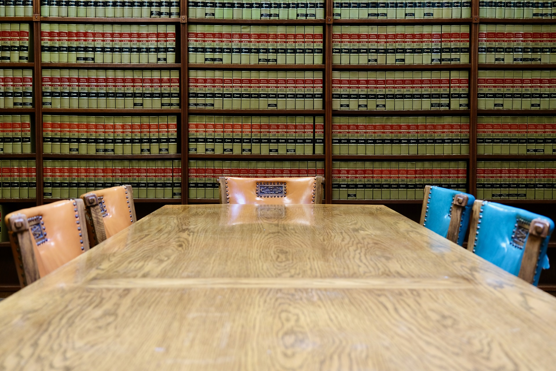 conference table with chairs in front of a wall of law books